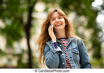 Close up of smiling young woman talking with mobile phone in park