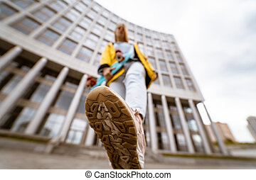 Close up of sneaker shoes of young woman on street