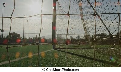 Close-up of soccer net on a field with a man running in the back