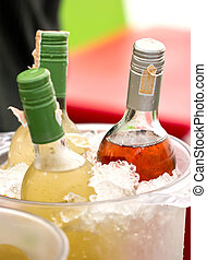 Close up of soft drink bottles in ice bucket.