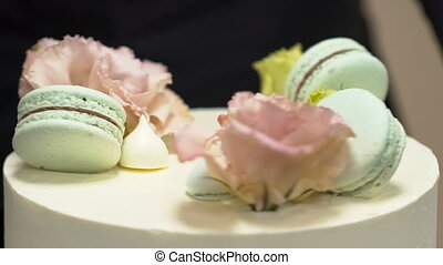 Close-up of spinning cake decorated with flowers and macaroons.
