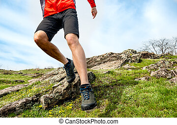 Close-up of Sportsman's Legs Running on Rocky Mountain Trail. Active Lifestyle and Adventure Concept