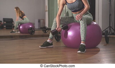 Close up of sportswoman lifting dumbbells in front of camera in the gym
