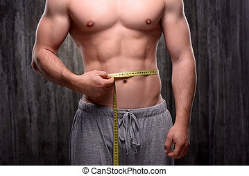 Close up of sporty man measuring his waist