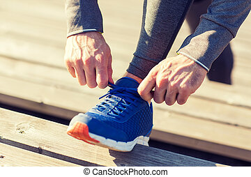 close up of sporty man tying shoe laces outdoors - fitness,...