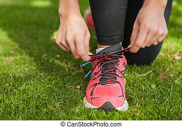 Close up of sporty woman tying her shoelaces