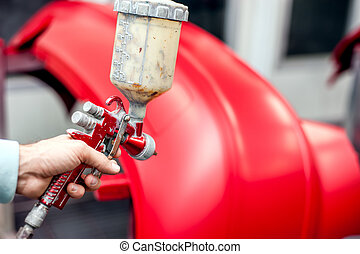 Close-up of spray gun with red paint painting a car in ...