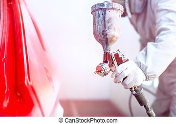 Close-up of spray gun with red paint painting a car in...