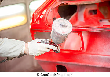 Close-up of spray paint gun painting a red car in painting ...