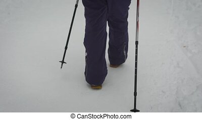 Close up of stepping legs of a woman in warm black trousers and heavy boots walking with ski poles in the forest. Female athlete demonstrating nordic walking on the path in winter nature outdoors.