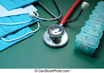 Close up of stethoscope, mask and pill box on green background