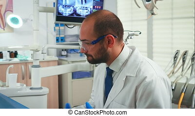 Close up of stomatologist talking with woman in dental clinic. Doctor and nurse working together in modern stomatological office explaining radiography of teeth from digital monitor in background
