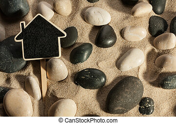 Close-up of stones and house sticking out of the sand in the sun