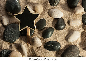 Close-up of stones and star sticking out of the sand in the sunl