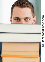 Close up of student hiding behind a stack of books