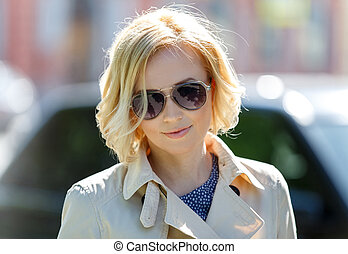 Close-up of stylish blond female model in sun glasses