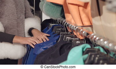 Close up of stylish lady choosing the coat in rich boutique
