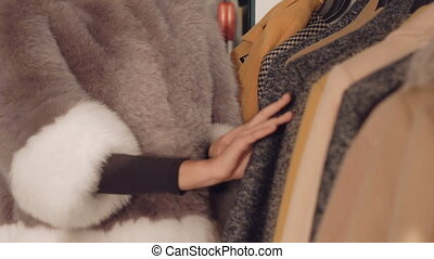 Close up of stylish lady choosing the fur coat in boutique