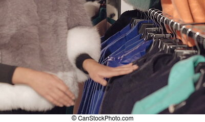 Close up of stylish lady choosing the coat in boutique