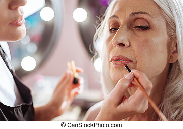 Close up of stylists hands applying lipstick to clients lips