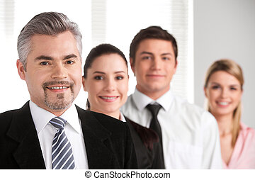 Close up of successful adult businessman leading business team. Looking and smiling at camera with blur background