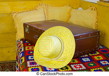 close up of summer straw women hat on old suitcase