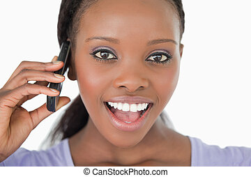 Close up of surprised looking young woman on the phone on white background