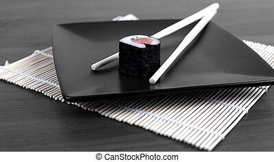 close-up of sushi and chopsticks on a wooden table