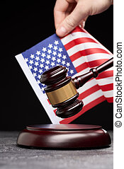Close up of symbol of law and court. Wooden gavel with hand on background of American flag on black background