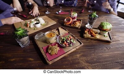 Close up of table served with assorted food setting on wooden platters. Image of different dishes and snacks on the brown surface with people and glasses of wine in the background.