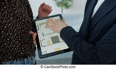 Close-up of tablet with apartment plan and hands broker and clients touching screen during business presentation. People and modern technology concept.