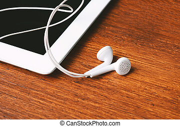 Close up of tablet with earphones on wooden table