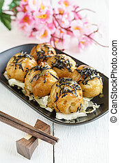 Close up of takoyaki on wooden table with chopsticks
