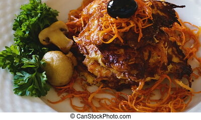 Close up of tasty fried carrot pancakes with mushrooms and ...