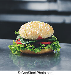Close-up of tasty veggie quinoa chickpeas burger with tomotoes,