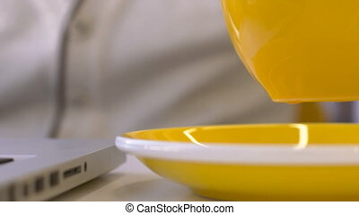 Close up of tea mug is being put onto the plate in moderm cafe.