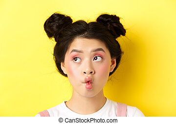 Close-up of teen asian girl pucker lips and looking funny at camera, standing with glamour makeup and stylish hairstyle, yellow background