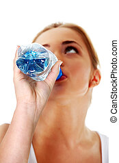 Close up of teen woman drinking mineral water from bottle.