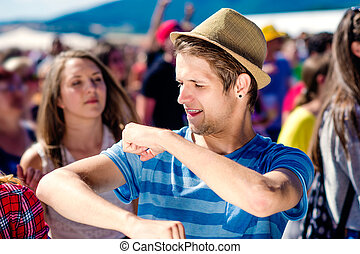 Close up of teenage boy at summer music festival under the stage in a crowd enjoying himself, dancing and singing