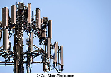 Close up of telecommunications cell phone tower with wireless communication antennas; blue sky background and copy space on the right