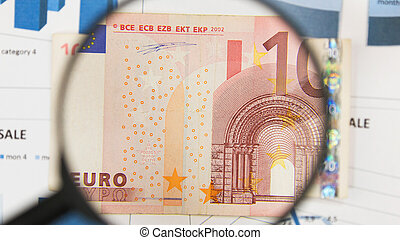 Close-up of ten euros through a magnifying glass. Business background. Money research concept.