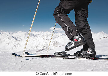 Close-up of the athlete's skier's foot in ski boots rises into the skis against the background of the snow-capped Caucasus mountains on a sunny day. Winter sports concept