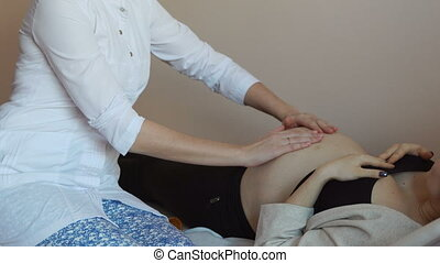 Close-up of the belly of the pregnant woman and the doctor's...
