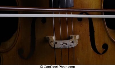 Close up of the bow touches the strings on a cello