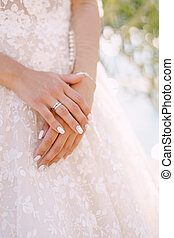 Close-up of the bride's hands with a wedding ring on a cream dress background. Fine-art wedding photo in Montenegro, Perast.