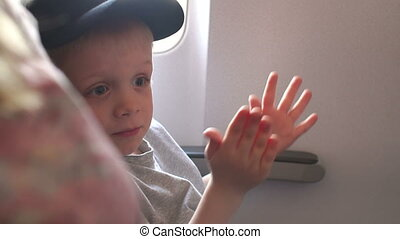Close-up of the child applauding on the plane after takeoff or landing.
