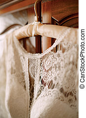 Close-up of the collar of the bride's dress on a hanger with shallow depth of field.