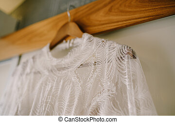 Close-up of the collar of the bride's dress on a wooden hanger against the wall.