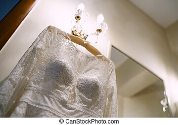 Close-up of the corset of the bride's wedding dress in a room with white walls and a wall lamp on.