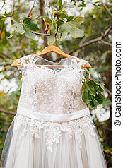 Close-up of the corset of the bride's wedding dress on a tree hanger on the branches.